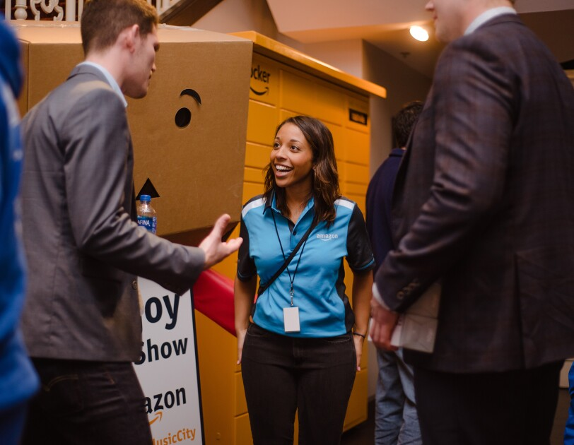 A woman wearing an Amazon-branded shirt speaks with two men at an event in Nashville.