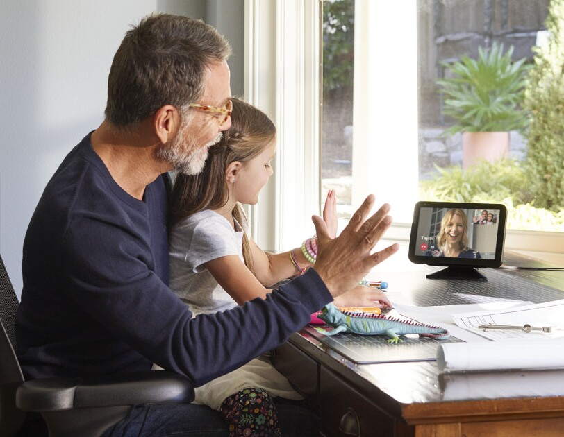 New Echo Show 8 device on a desk, shows a man and young child interacting with another person on the screen.