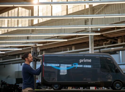Ein Rivian Mitarbeiter putzt das maßstabgetreue Modell des Fahrzeugs bis es glänzt.
