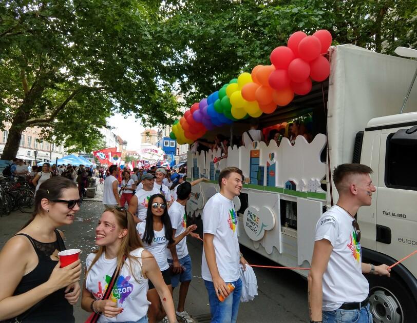 Amazon Mitarbeiter feiern neben dem Glamazon-Wagen auf dem Christopher Street Day in München.