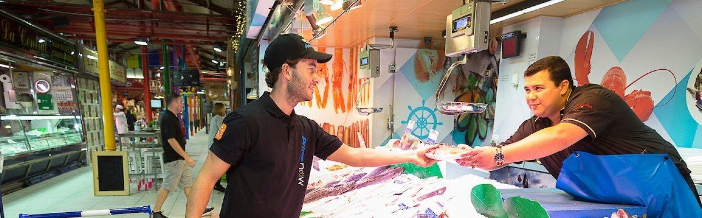 Mercado de La Paz de Madrid. Trabajador de Prime Now recoge en una pescadería el paquete de un cliente. El pescadero, con un delantal azul, tiene que incorporarse para entregarle el pedido. El trabajador de Prime Now va con un carro de la compra que contiene más pedidos.