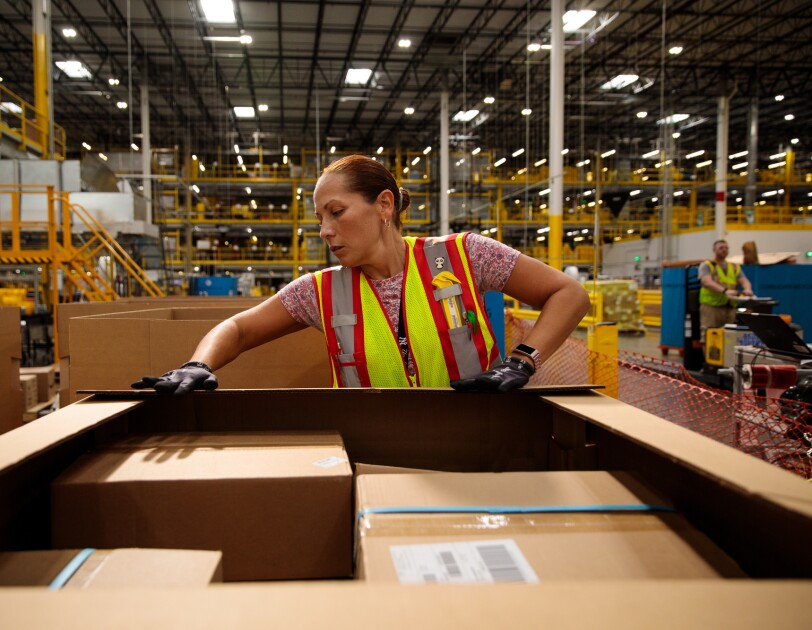 A woman in a safety vest works in a warehouse space.