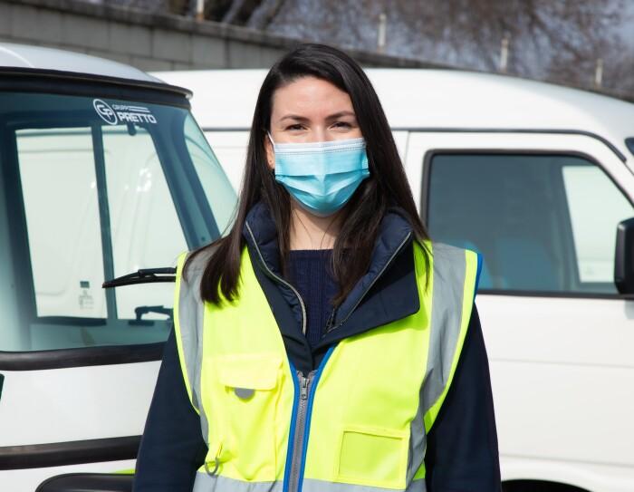 Micaela Moscarella posa davanti ad alcuni veicoli elettrici per le consegne Same Day