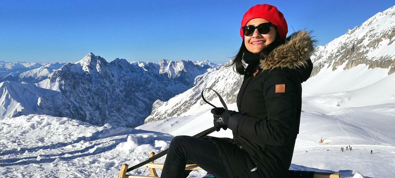 Mehak in den Alpen beim Schlitten fahren. Sie trägt eine rote Pudelmütze und eine Sonnenbrille. Im Hintergrund sieht man die schneebedeckten Alpen.