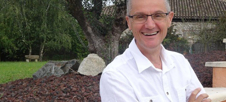 Utroi Wendall se tient devant une maison de pierre et un arbre à la campagne