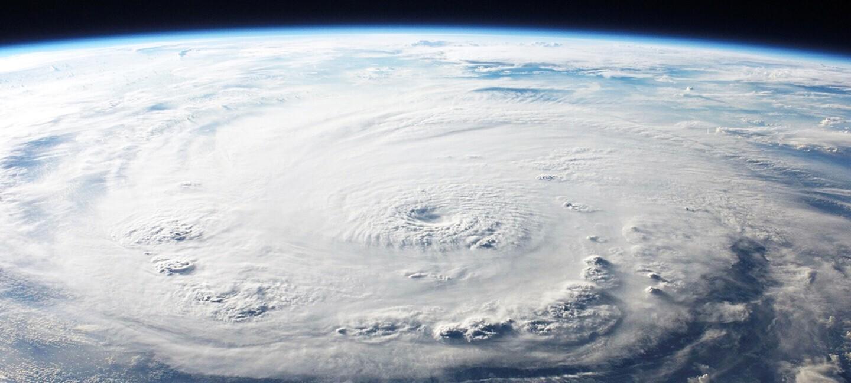 Foto de la tierra desde el espacio. Se ven nubes de color blanco y azul. También se ve una parte de cielo oscuro.