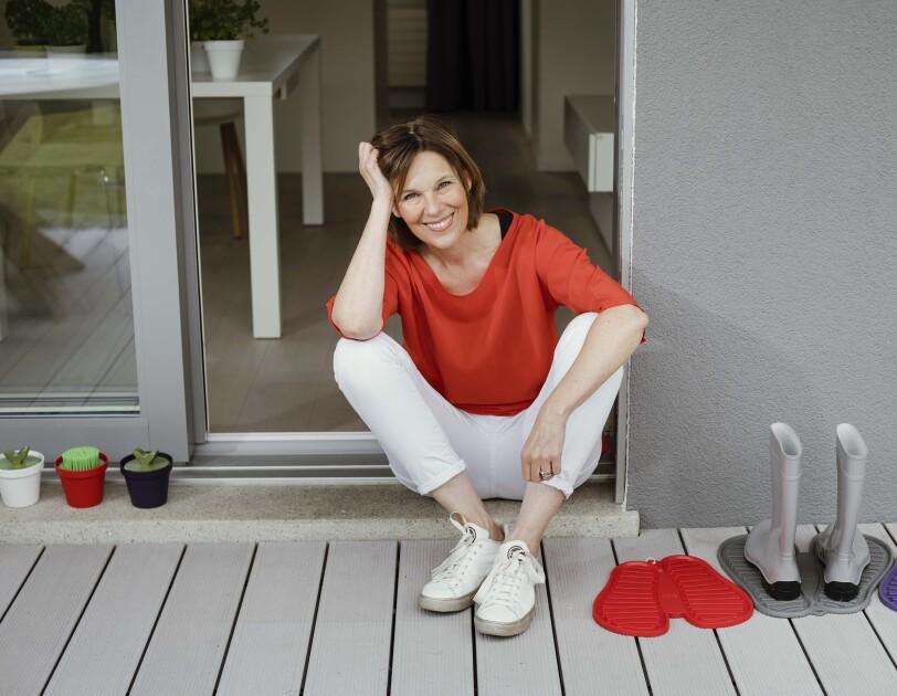 Eine Frau mit rotem T-shirt und weißer Hose sitzt in einem Türrahmen und lächelt in die Kamera.