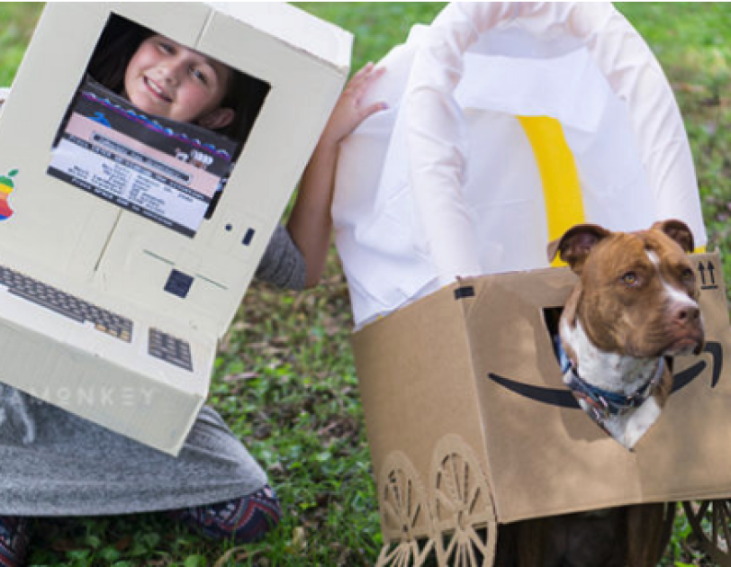 Halloween costume made out of Amazon boxes. On the left, a little girl wears a  gray dress and a homemade apple computer from the 1980s. To her left is a dog in an Amazon box made to look like a covered wagon.