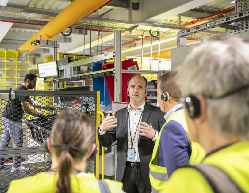 Ein Herr im Anzug steht vor einer Arbeitsstation im Logistikzentrum und erklärt Besuchern in gelben Besucherwesten den Ablauf