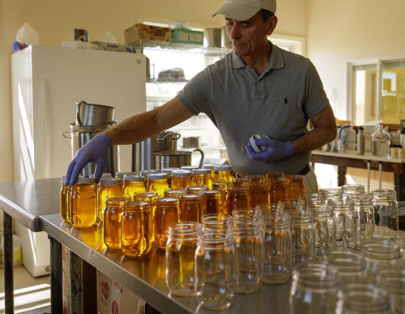 A man arranges a row of jars.