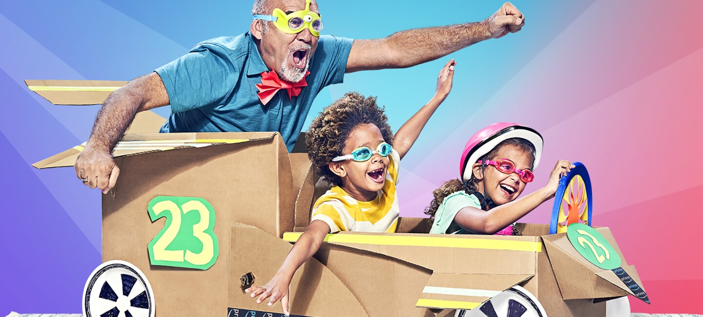 """Two children and a man appear joyful as the """"ride"""" in a cardboard box car."""