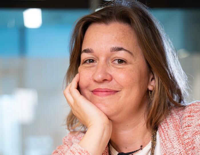 Marta Fernández, Content Program Manager de Alexa delante de un dispositivo Amazon Echo. Está apoyada en una mesa con un brazo en la mejilla. LLeva una camiseta blanca y una chaqueta rosa. Además lleva un collar de color de oro. Tiene media melena rubia.