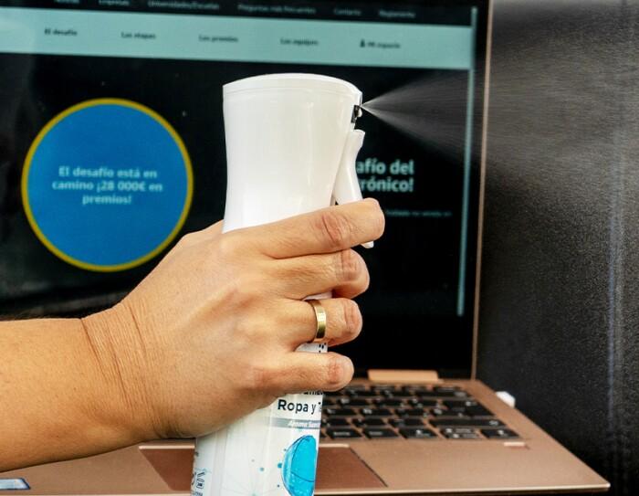 Una mano sujeta un espray elominador de olores. De fondo un ordenador con este mensaje en la pantalla: El desafío está en camino. ¡20 000 euros en premios!