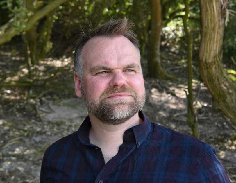 Headshot of David Atkinson standing in the woods, looking into the distance