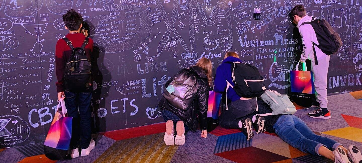 AWS GetIT students drawing on a giant blackboard which is filled with messages and doodles.