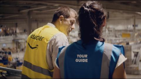 Screenshot aus dem TV-Spot: Man sieht einen Besucher mit gelber Sicherheitsweste, der mit einem Tour Guide redet. Beide sind von hinten zu sehen. Vor ihnen breitet sich die riesige Halle eines Logistikzentrums aus.