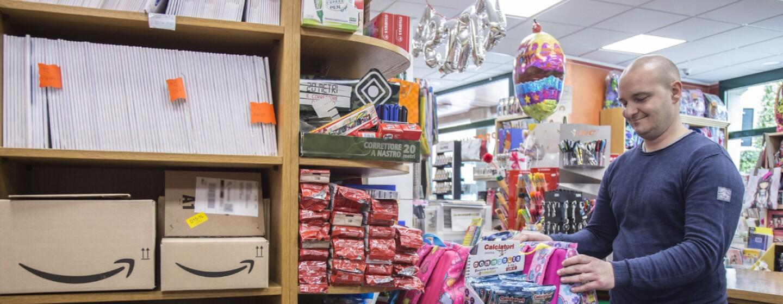 Andrea Locatelli all'interno della cartoleria Teresa di Chiuduno, circondato da prodotti, oggetti regalo e pacchi Amazon.