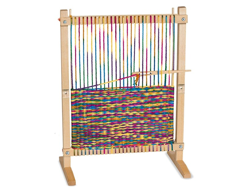 Wooden weaving loom, with loomed article partially completed with rainbow-colored threads.