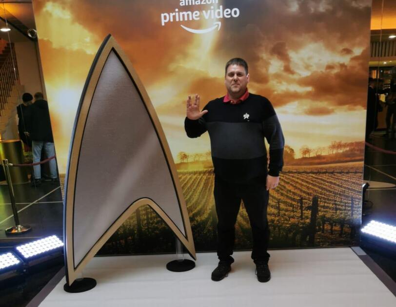 Ein Mann mit Star Trek Logo am Revers steht neben einem lebensgroßen Star Trek Logo und posiert fürs Foto.