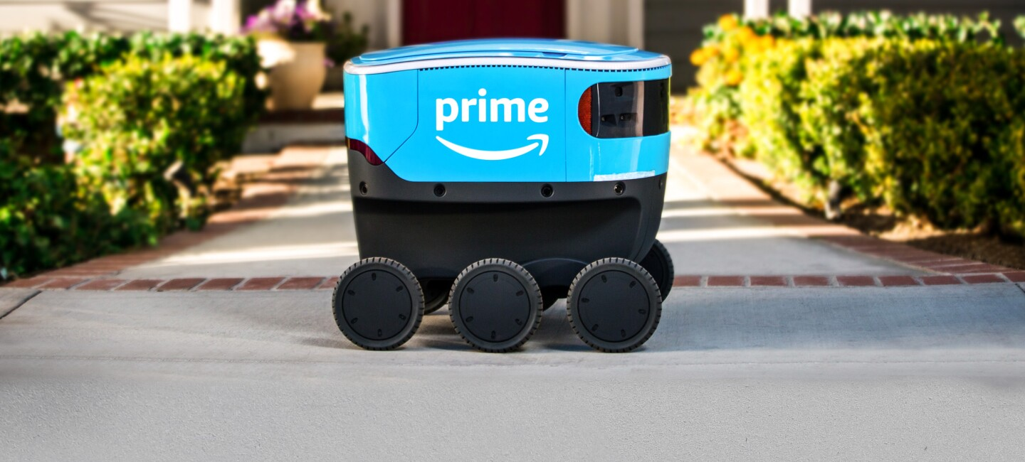 A bright blue, sleek, six-wheeled Amazon Scout delivery robot parked on the concrete walkway of an American home
