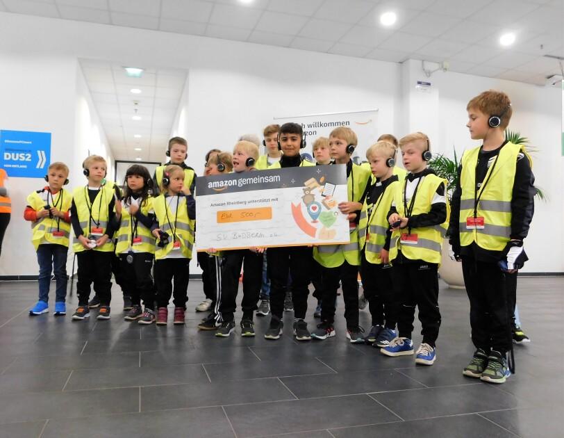 Eine Gruppe von Kindern, eines hält einen Spendenscheck