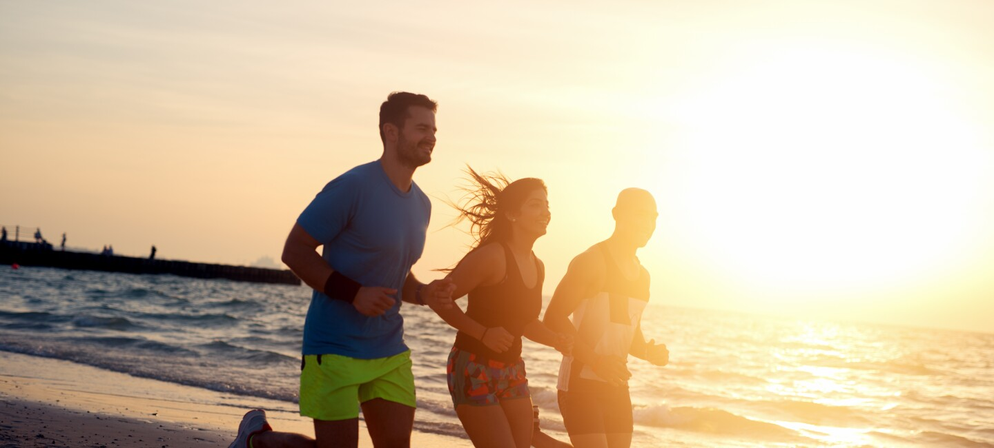 Two men and a woman run on a beach at sundown.