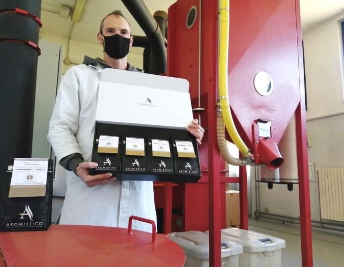 Un uomo in un sito di produzione di caffè indossa un camice bianco e una mascherina protettiva sul volto. Regge in mano un espositore di confezioni di caffè in polvere.