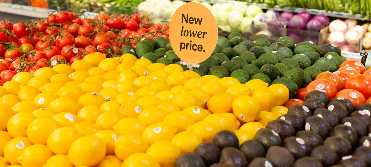 "Inside a Whole Foods Market store, lemons, limes, avocados, and tomatoes are stacked on a table, with a ""New lower price"" sign in the center of the produce. Behind the display, lettuces, peppers, squash and other vegetables are stocked in a produce wall display."