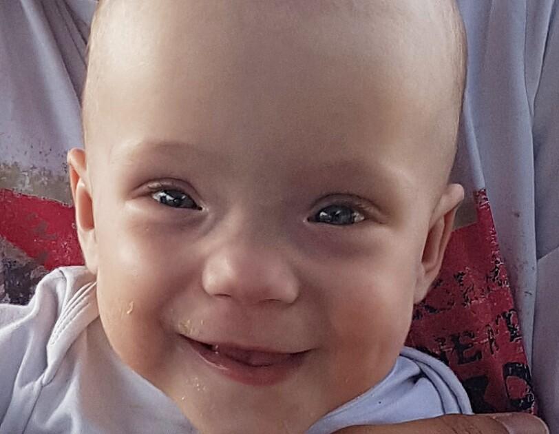 Lena ist ein kleines Baby. Sie hat große Augen und lacht in die Kamera.