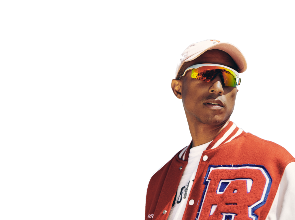 The artist Pharrell stands on a white background wearing sunglasses and a hat.