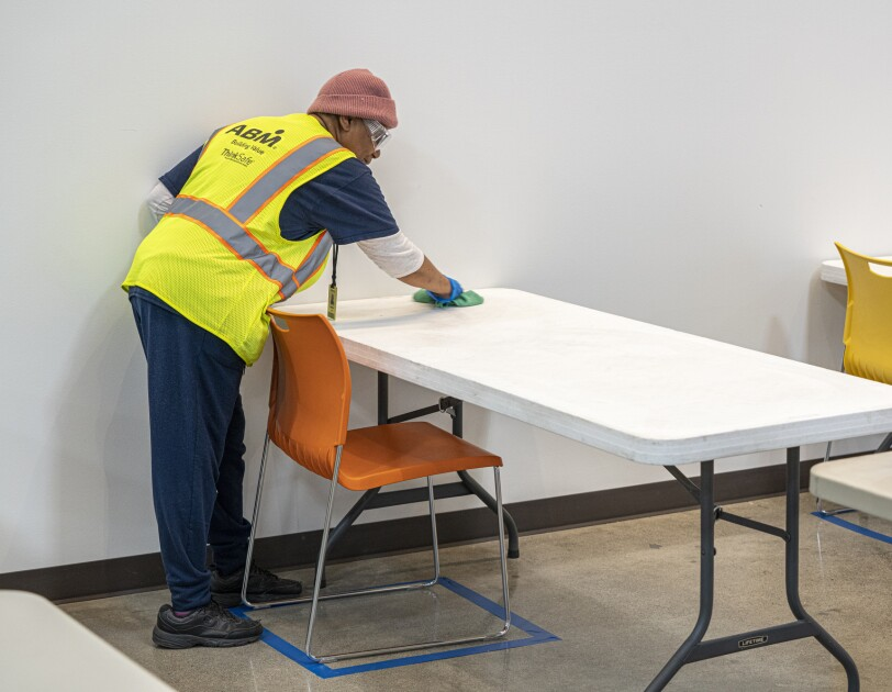 A man in a safety vest uses a cleaning cloth to sanitize a white plastic table.