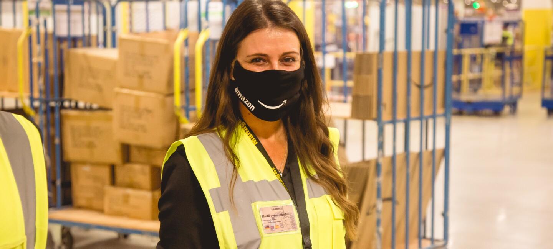 Eine lächelnde junge Frau hinter Gesichtsmaske