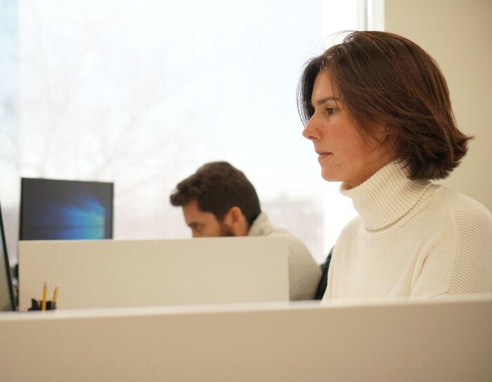 Amazonian de una oficina corporativa trabaja mirando atentamente la pantalla del ordenador. Viste un jersey de cuello alto y color blanco y tiene media melena.