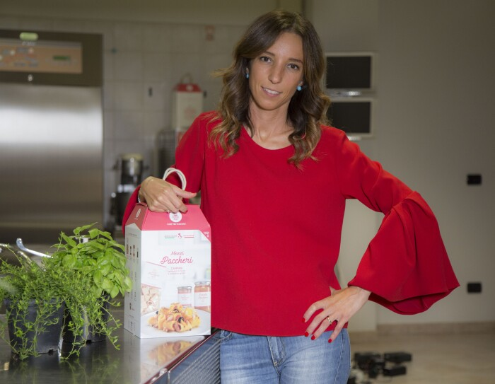 Ritratto della sviluppatrice dei prodotti My Cooking Box. La ragazza si trova in una cucina, veste una maglia rossa e tiene una box sotto il braccio destro. Accanto alla box, una pianta di basilico e una di timo. Sullo sfondo, un frigorifero industriale.
