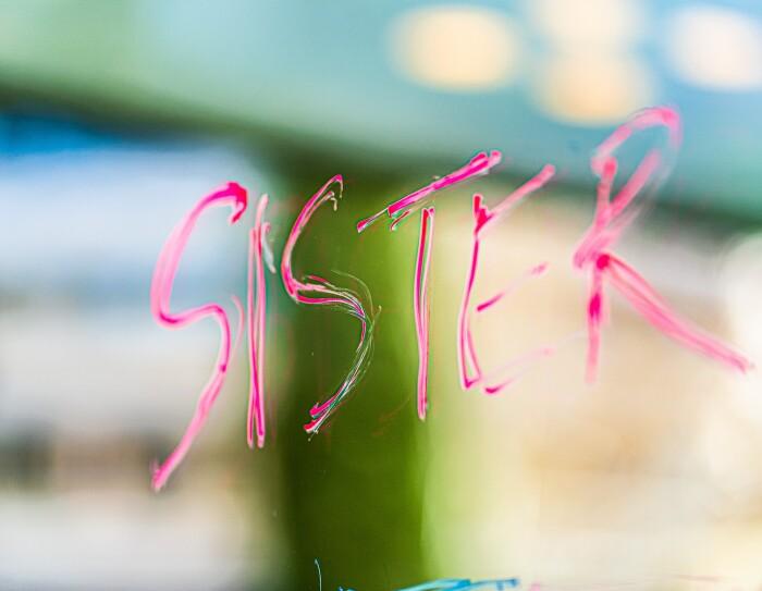 En un cristal con el paisaje de fondo desenfocado, está en color rosa escrita la palabra Sister.