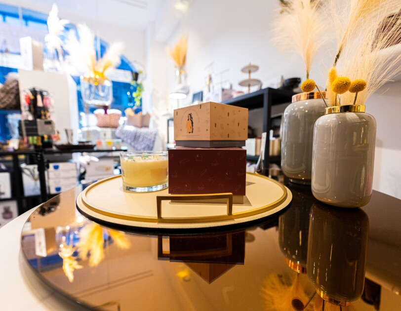 Auf einem goldenen Tisch stehen Deko-Elemente, unter anderem Vasen und Kerzen sowie ein weißes Tablett.