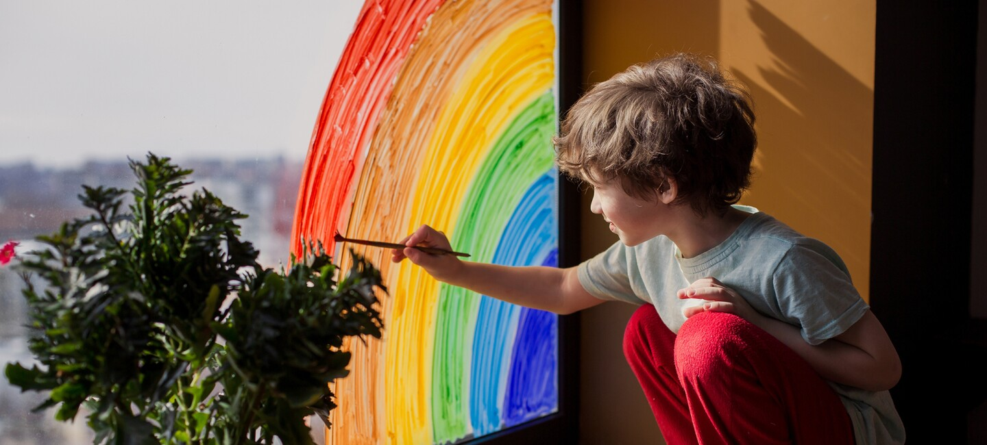 A child placing homemade rainbows in the window of their home, during COVID-19 pandemic.