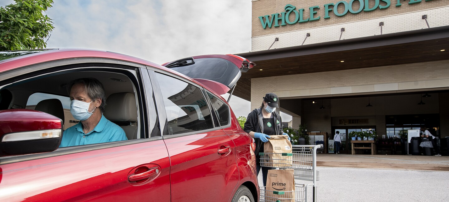 A man wearing a face mask receives an online order of groceries from Whole Foods Market, delivered to the trunk of his car.