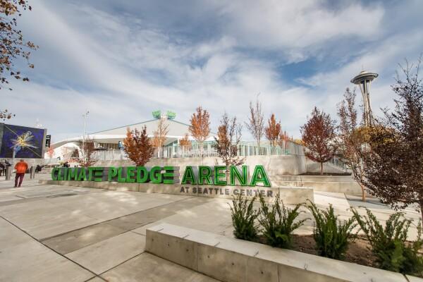 Climate Pledge Arena a Seattle, EE.UU. Parte exterior del estadio cubierto. Aparece en letras grandes y de color verde Climate Pledge Arena at Seattle Center en primer plano. De fondo el estadio. el suelo es de mármol y hay árboles de color marrón.