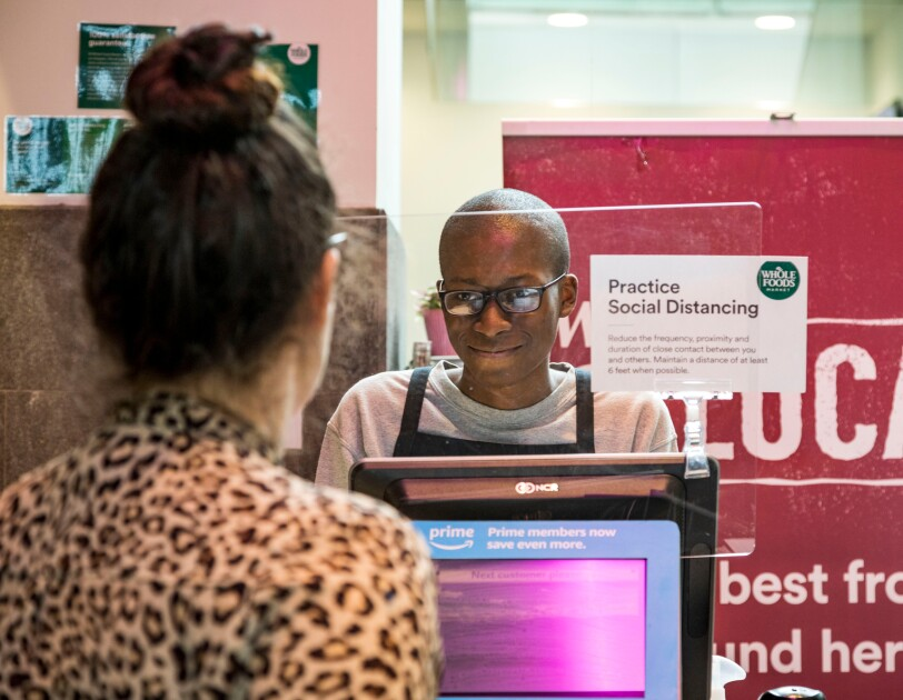 "A supermarket cashier looks at a customer. The cashier is behind a clear barrier and a sign with the Whole Foods Market logo and the words ""Practice Social Distancing."""