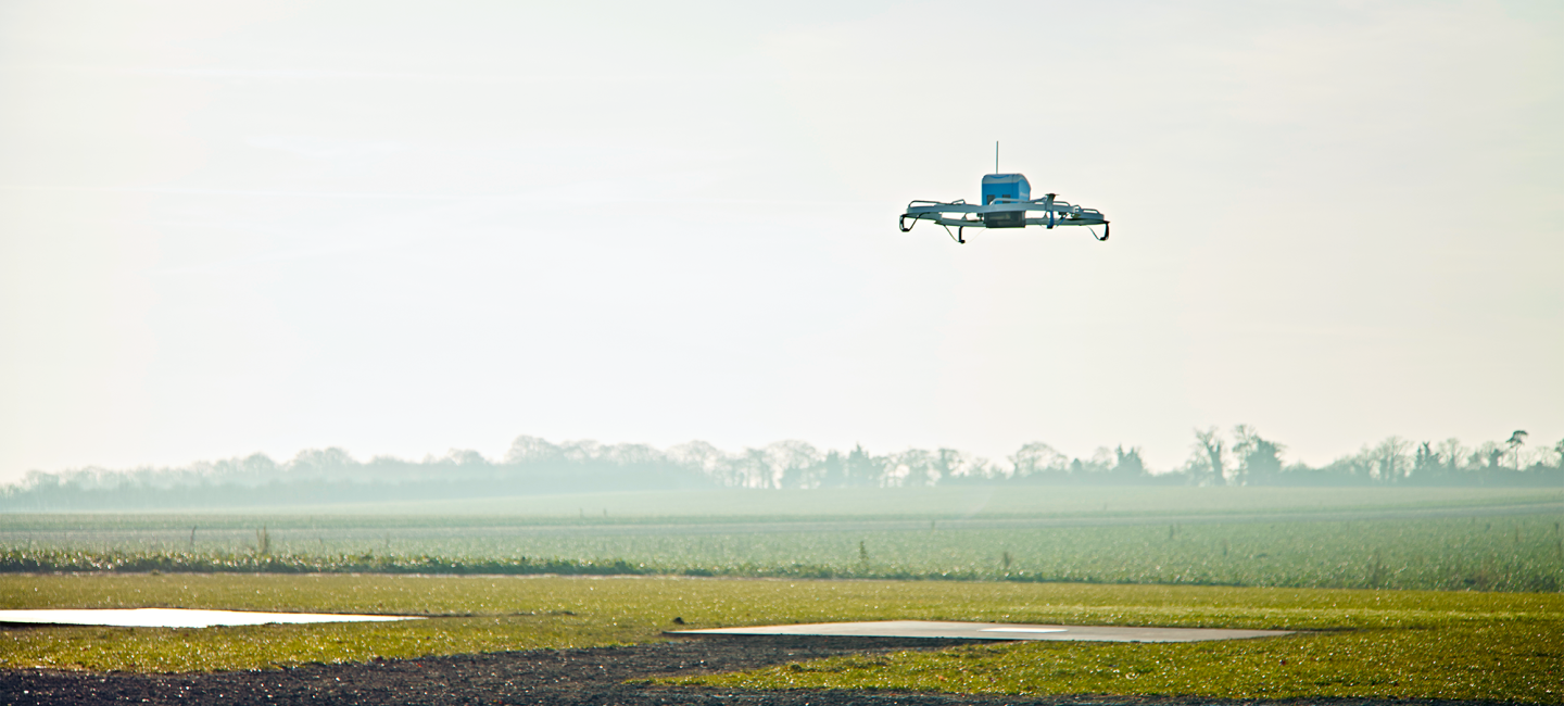 An Amazon Prime Air drone prototype flying over a field