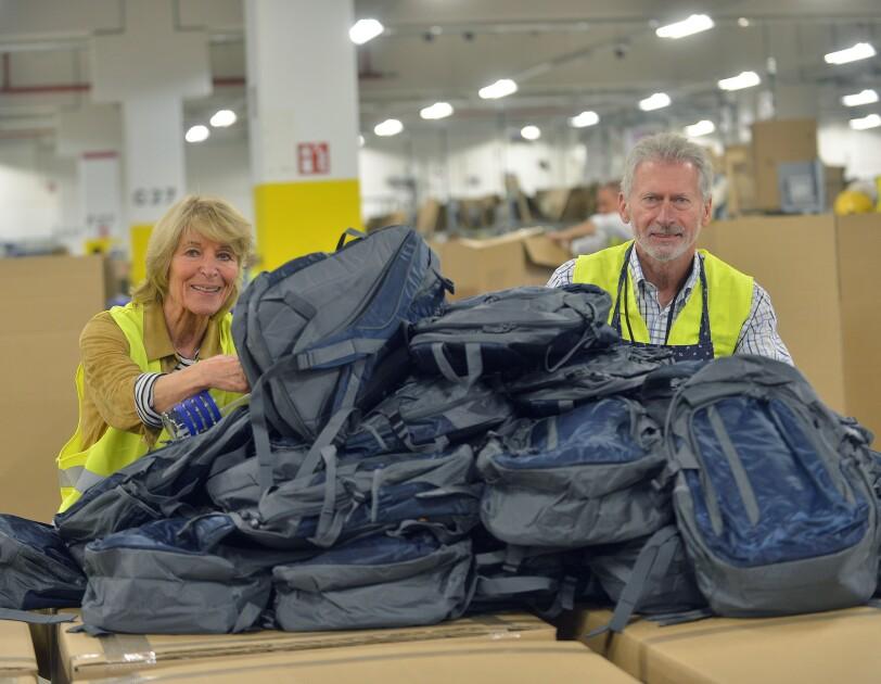 Eine blonde Dame in mittleren Jahren ist mit Paul Breitner zu sehen. Beide stützen sich auf Karton, auf den Karton liegen diverse Rucksäcke.