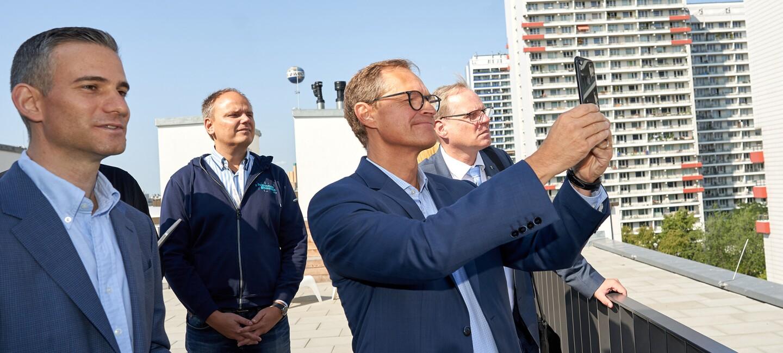 Der Bürgermeister von Berlin, Michael Müller, steht mir den Amazon Kollegen auf dem Dach den Amazon-Gebäudes. Sie genießen die Aussicht und machen Fotos der Skyline.