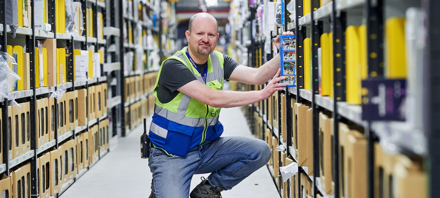 Operations Apprentice, Norman Quigg, pictured kneeling in an aisle at an Amazon fulfilment centre and pulling out a product while looking at the camera.
