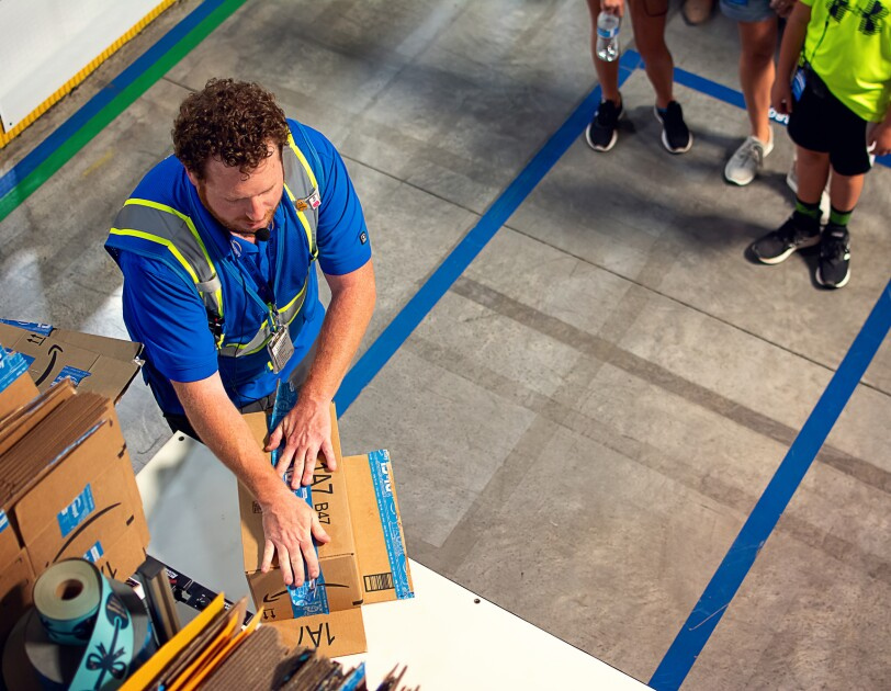 A man in a safety vest applies packing tape to a cardboard box.