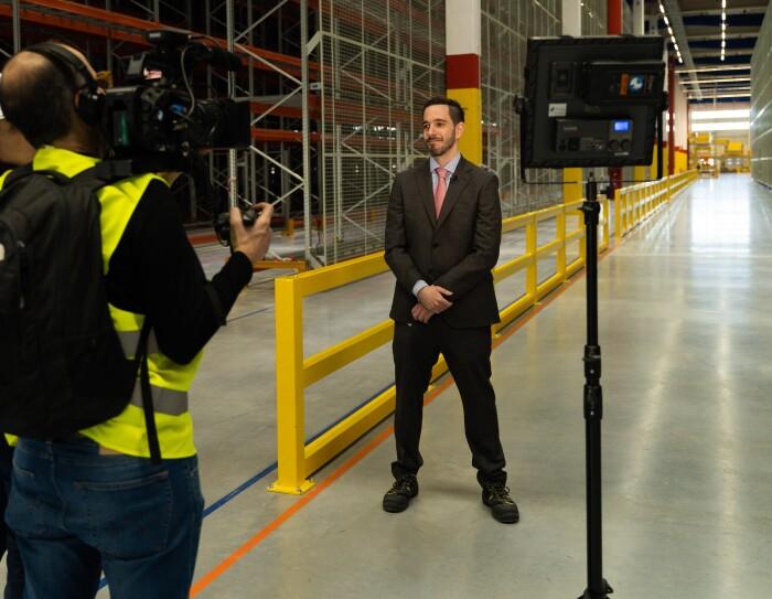 Nacho Ferreiro, responsable del centro, en un momento de la grabación. En primer plano aparece un foco, un cámara y una productora. En segundo plano, Nacho Ferreiro, con traje y corbata, botas de seguridad.