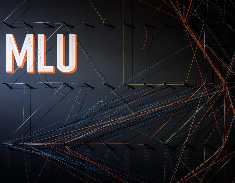 "Various colors of string criss cross on a dark wall decorated with the letters ""MLU."""