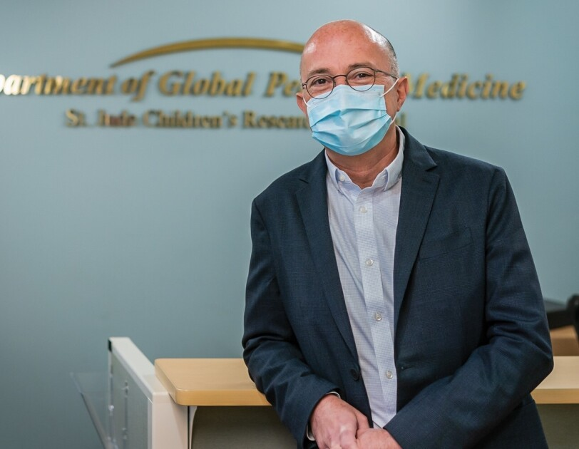 A photo of Dr. Galindo, childhood cancer researcher and physician, wearing a surgical mask and smiling in front of a desk at the St. Jude Children's Research Hospital.