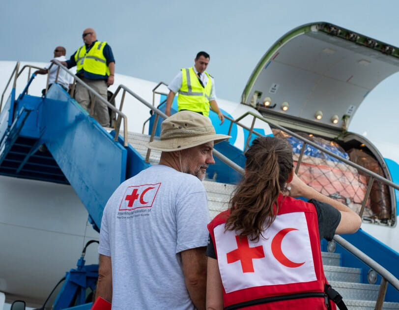 An airplane in the background with people in the foreground who are wearing clothing that bears the image of a red cross next to a red crescent.