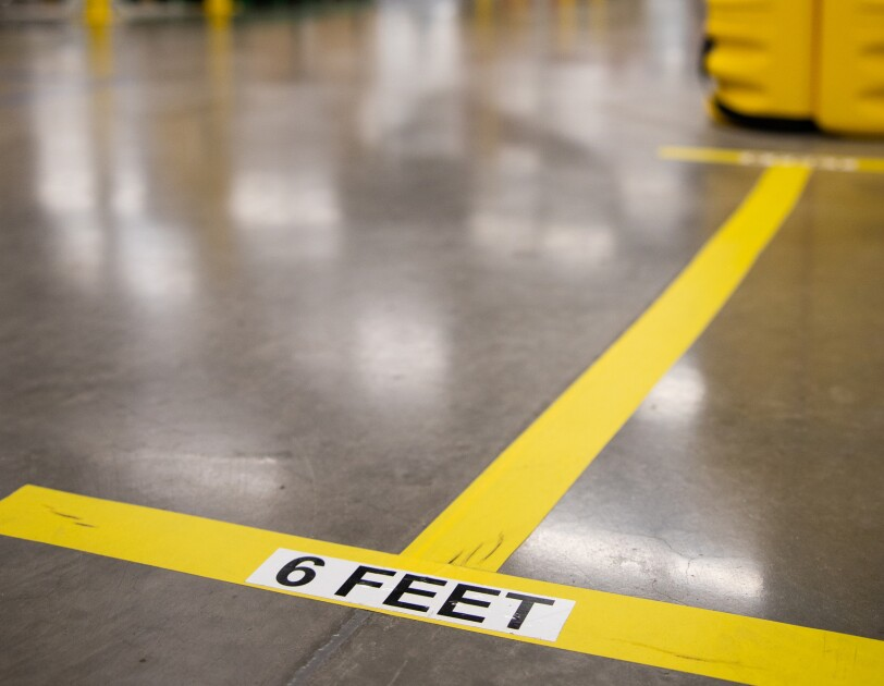 "Markings on a concrete floor in a workplace say ""6 FEET"""